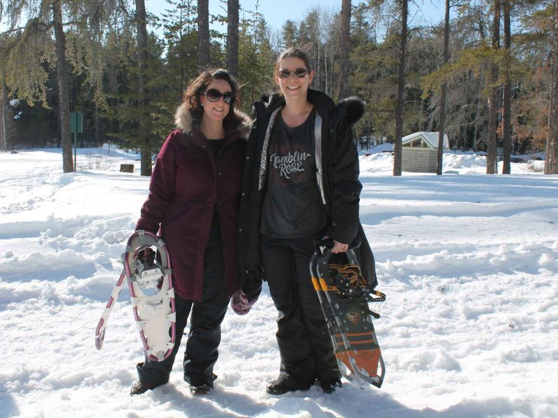 two women preparing to go snowshoeing