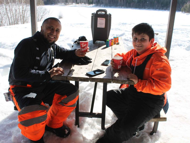 father and son enjoying hot chocolate at winter hiking day