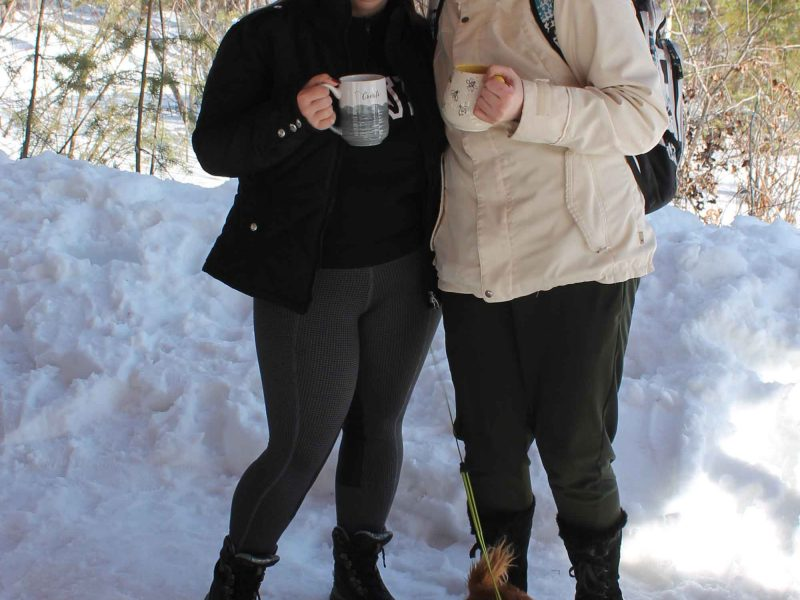 two women enjoying hot chocolate at winter hiking day