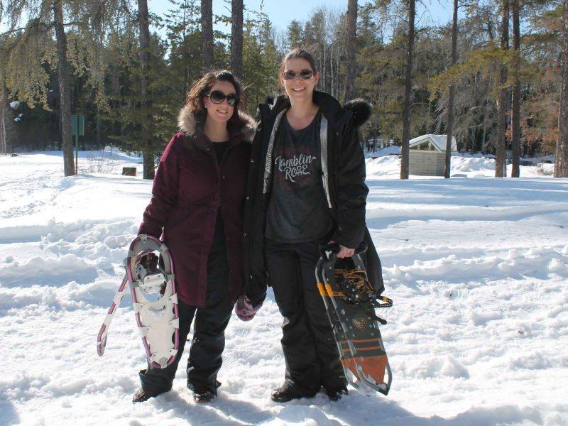two women preparing to go snowshoeing