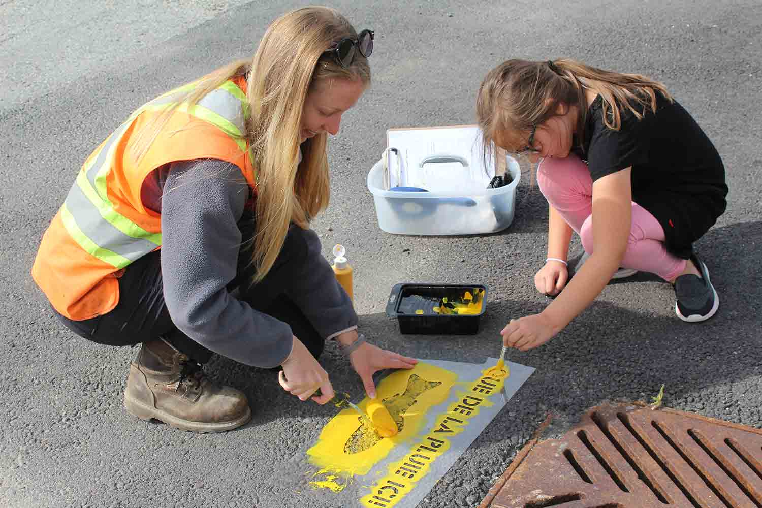 Volunteer and student painting yellow fish near a storm drain